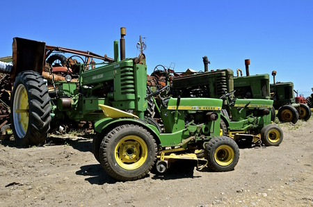 BARNSVILLE, MINNESOTA, June 15, 2016: The worn-out tractors and riding lawn mowers found in a junkyard are products of John Deere Co, an American corporation that manufactures agricultural, construction, forestry machinery, diesel engines, and drivetrains Editorial