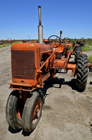 junkyard: An old orange tractor is parked in salvage and a junkyard