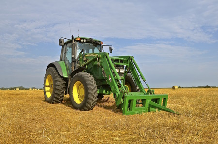 john deere: ROSHOLT, SOUTH DAKOTA; August 15, 2015: The new tractor and spear bale loader are products of John Deere Co, an American corporation that manufactures agricultural, construction, forestry machinery, diesel engines, and drivetrains. Editorial
