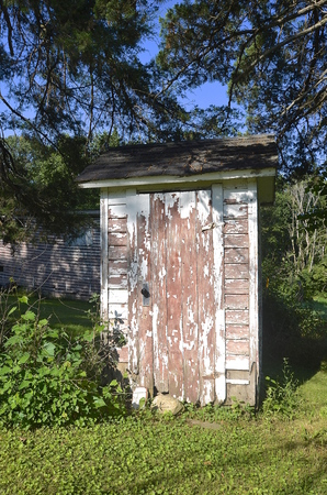 latrine: An old  white outhouse with peeling paint and surrounded by trees and bushes