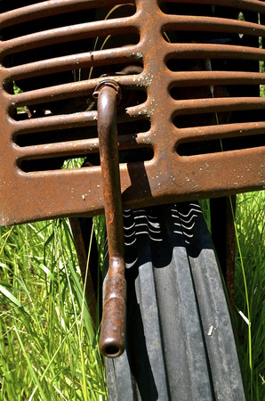 protruding: An old tractor leaning on its one tire with a crank protruding from the grill Stock Photo