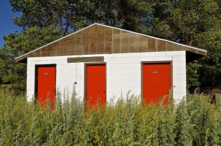 latrine: Colorful deserted camping washroom facilities surrounded by uncut weeds and grasses