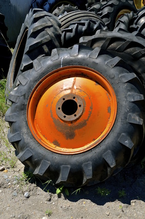 lugs: An orange wheel or rim for an old tractor is leaning against a pile of tires