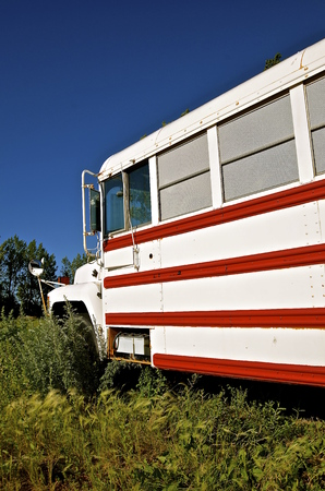 converted: An old school bus painted red and white is converted into a camper