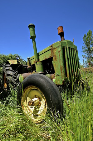 Old green tractor left standing in the long green grass