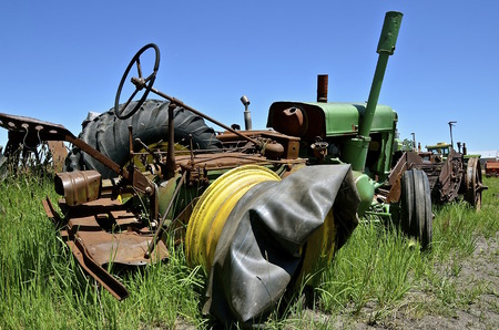 inner tube: An old tractor without a tire and inner tube laying on the rim.