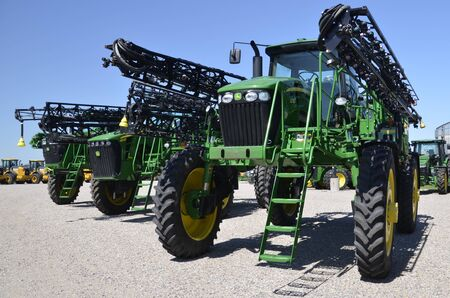 john deere: MOORHEAD, MINNESOTA, July 25, 2016: The new tractor sprayer with long booms is a product of John Deere Co, an American corporation that manufactures agricultural, construction, forestry machinery, diesel engines, and drivetrains.
