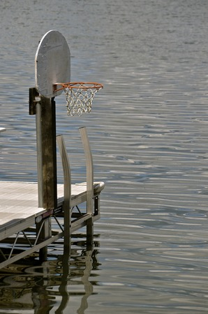allowing: A backboard, net, and rim are located on the end of a dock, allowing for water basketball