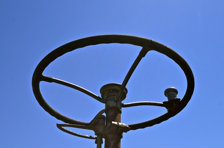 throttle: The steering wheel of an old tractor, throttle get, and knob are silhouetted against the blue sky. Stock Photo