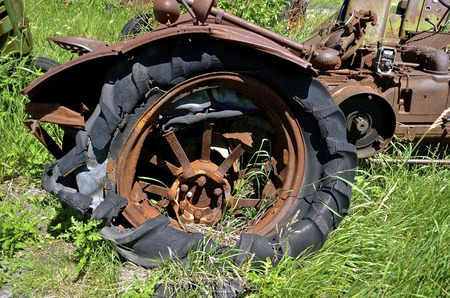 flat tire: Rotten flat tire on a very old rusty tractor with a crumpled fender Stock Photo