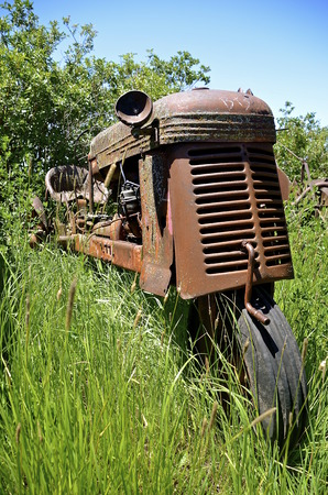 An old one wheeled orange tractor with a crank is surrounded by long grass