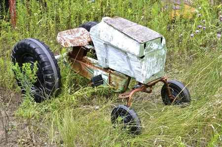lacking: The homemade pedal tractor in the long grass is lacking a steering wheel Stock Photo