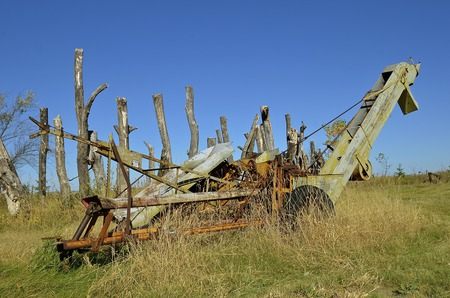 picker: An old one row corn picker run by a power takeoff sits in the woods and weeds,