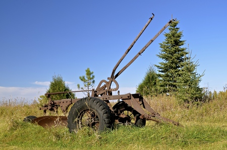 Parked in the grass is a vintage long levered two bottom trip plow which would unhook if hitting a large rock when plowing a field.