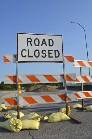 road closed: Sand bags hold a ROAD CLOSED sign upright at a road construction site.