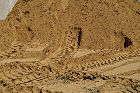 tyre tread: Tire tracks of heavy equipment are evident on the sand of a huge pile to be used in a construction site.