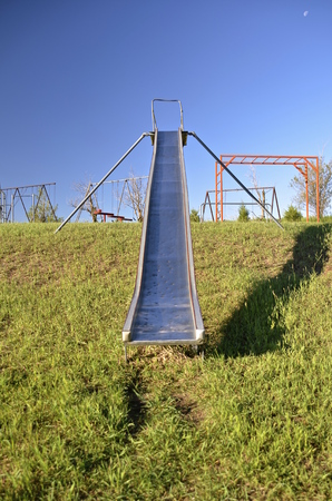totter: Old metal slippery slide on the hillside of a school yard playground