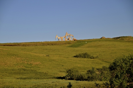 Rigs pumping oil in the rolling plains of the Bakken Fields in North Dakota
