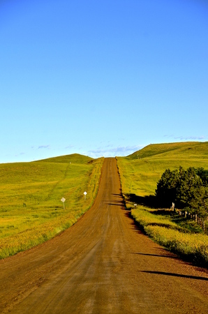 scoria: The early morning sun shines on a rural country road which leads uphill into the horizon of the western prairie of North Dakota Stock Photo