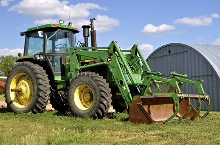 deere: WATFORD, NORTH DAKOTA, June 26, 2016: The John Deere 740 tractor and front end hay loader are products of John Deere Co, an American corporation that manufactures agricultural, construction, forestry machinery, diesel engines, and drivetrains.