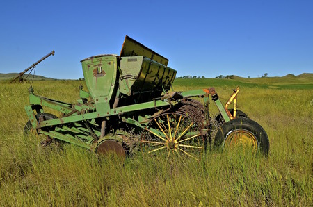 implementing: An old grain seeder with wide open seed boxes is left neglected in a grassy field.