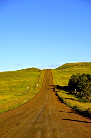 scoria: Rural country road covered with scoria rock leads uphill in western North Dakota