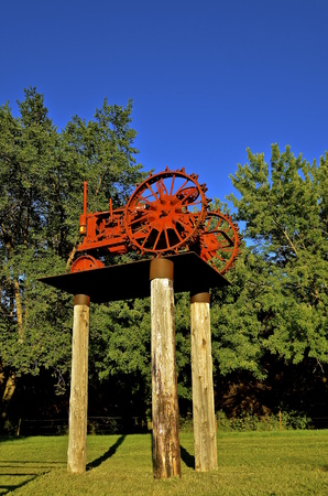 lugs: MADISON, SOUTH DAKOTA, August 20, 2016: The F-12 Farmall tractor is  perched high on the entrance to the Prairie Village Heritage Park which comes alive with displays of old tractors, farm machinery, and the life of early South Dakotans each third weekend