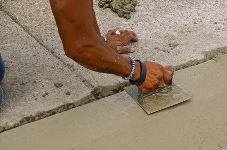Construction worker trowels wet cement