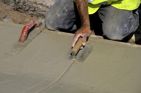 plasterwork: Construction worker on hands and knees spreads wet cement