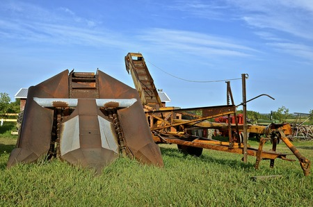 An old rusty two row corn picker required to be pulled by a tractor with power take off Stock Photo