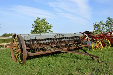seed drill: An old grain drill with a metal box to hold seed for planting small grain is parked in the grass.