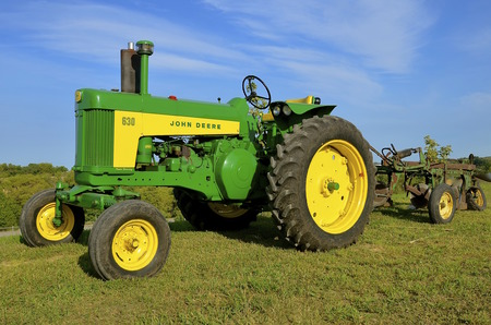 refurbished: ROLLAG, MINNESOTA, Sept 1: A  Restored  John Deer 630 two cylinder tractor pulling a plow is displayed at the West Central Steam Threshers Reunion(WCSTR) where 1000s attend each Labor Day weekend in Rollag, MN each year.