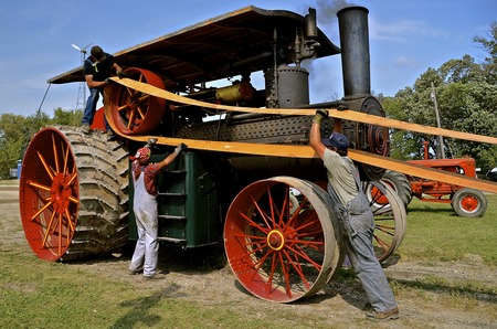ROLLAG, MINNESOTA, Sept 1. 2016: Uidentified men demonstrate the placing  of a belt on an old  steam engine fly wheel during the West Central Steam Threshers Reunion in Rollag, MN. Editorial