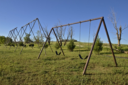play the old park: Three old swingers in a rural country school playground Stock Photo