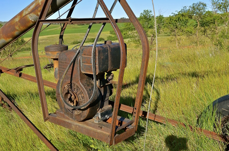 Gas engine which powered on old rusty tube grain elevator