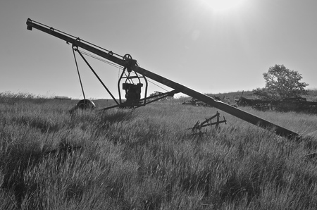 engine powered: A silhouetted old tube grain elevator powered by  a suspended gas engine is left in the long grass of a hilly pasture.