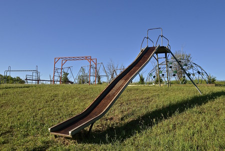 school yard: An old metal slippery slide in a school yard with equipment in the background