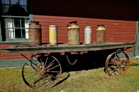 carreta madera: Varios antiguos de la leche y de escopeta latas oxidadas están en una plataforma de un viejo vagón de madera con ruedas de acero. Foto de archivo