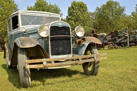 ROLLAG, MINNESOTA, 1 september 2016: De voorkant van een oude auto van Model T Ford wordt weergegeven tussen de dorsmachines op de West Central Steam Threshers Reunion in Rollag, MN bijgewoond door 1000's jaarlijks gehouden op Labor Day weekend.