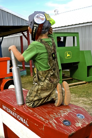 ROLLAG, MINNESOTA, Sept 1. 2016: An unidentified young boy plays on the wood International tractor at the West Central Steam Threshers Reunion in Rollag, MN attended by 1000s held annually on Labor Day weekend.
