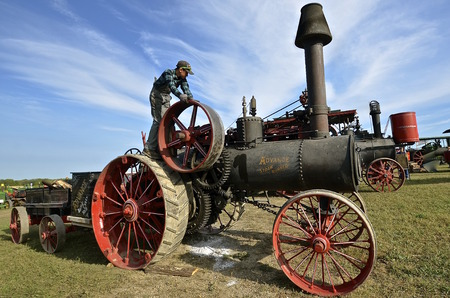 ROLLAG, MINNESOTA, Sept 1. 2016: An unidentified young lad works on an Advance Straw Burner vintage steam engine at the West Central Steam Threshers Reunion in Rollag, MN attended by 1000s held annually on Labor Day weekend.