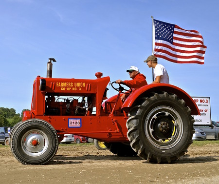 mn: ROLLAG, MINNESOTA, Sept 1. 2016: Two unidentified men operate an old restored Farmers Union Co-op No. 3 tractor in a parade at the West Central Steam Threshers Reunion in Rollag, MN attended by 1000s held annually on Labor Day weekend. Editorial