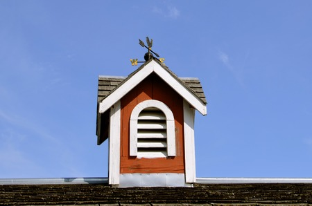 displays: The roofline of a barn displays a wooden cupola with a wind vane