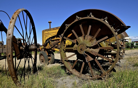 An old yellow tractor with rusty steel spoked and lugged wheels Stock Photo