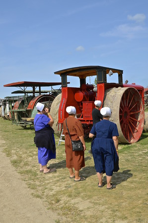 engine bonnet: ROLLAG, MINNESOTA, Sept 1. 2016: Unidentified Hutterite Colony women study a restored Avery tractor displayed displayed at the annual WCSTR farm show in Rollag held each Labor Day weekend where 1000s attend.