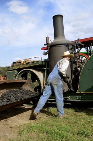 engine powered: ROLLAG, MINNESOTA, Sept 1. 2016: An unidentified man shovels coal into the boiler of a Buffalo Springfield steam engine displayed at the annual WCSTR farm show in Rollag held each Labor Day weekend. Editorial