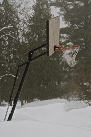 An outdoor leaning basketball standard, backboard, and hoop are surrounded by drifts of snow Stok Fotoğraf