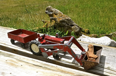 front end loader: Vintage toy red tractor pulling wagon with a front end loader filled with rocks rests on a weathered bench Stock Photo