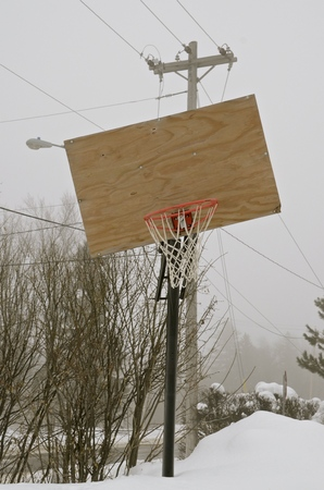 backboard: A crooked basketball backboard surrounded by high line wires sets in a deep snowbank on a foggy day