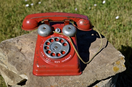 An old toy childs dial telephone left on a rock outside. Stock Photo